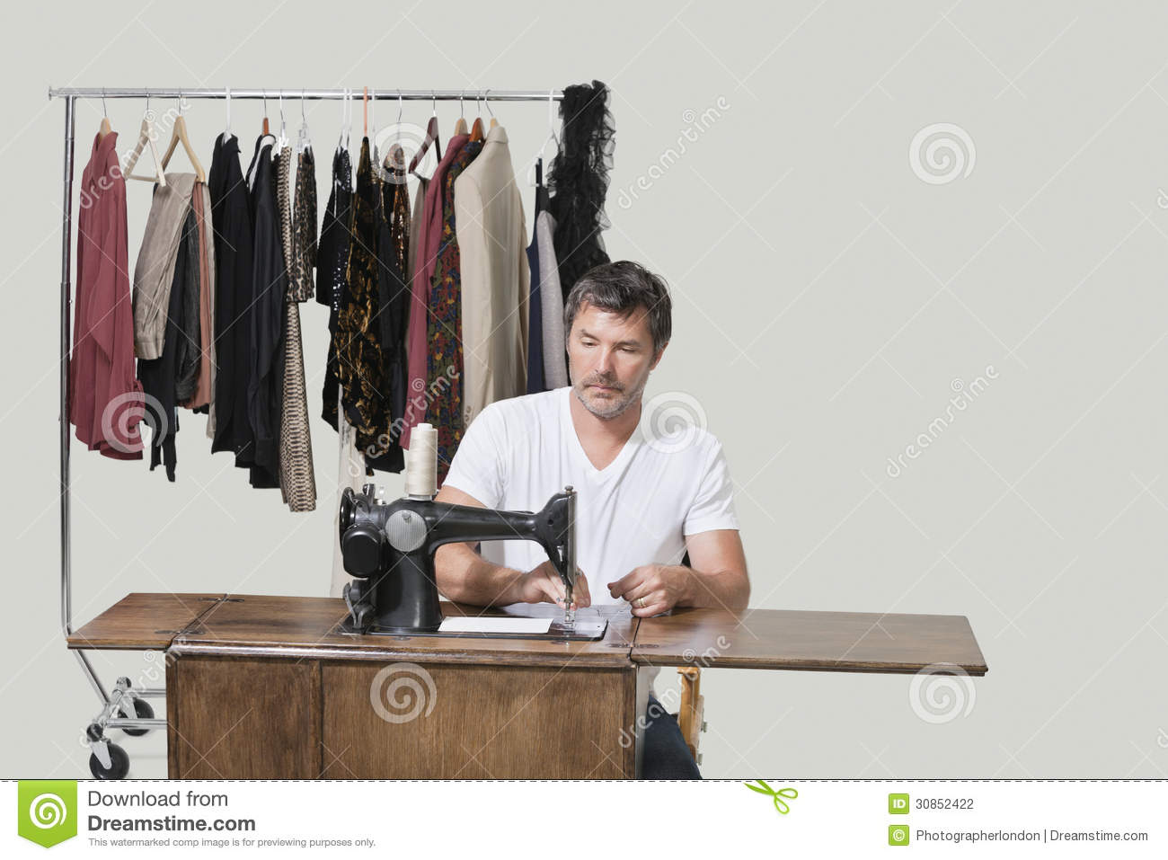 Stock Photography: Mature male dressmaker sitting at sewing machine ...