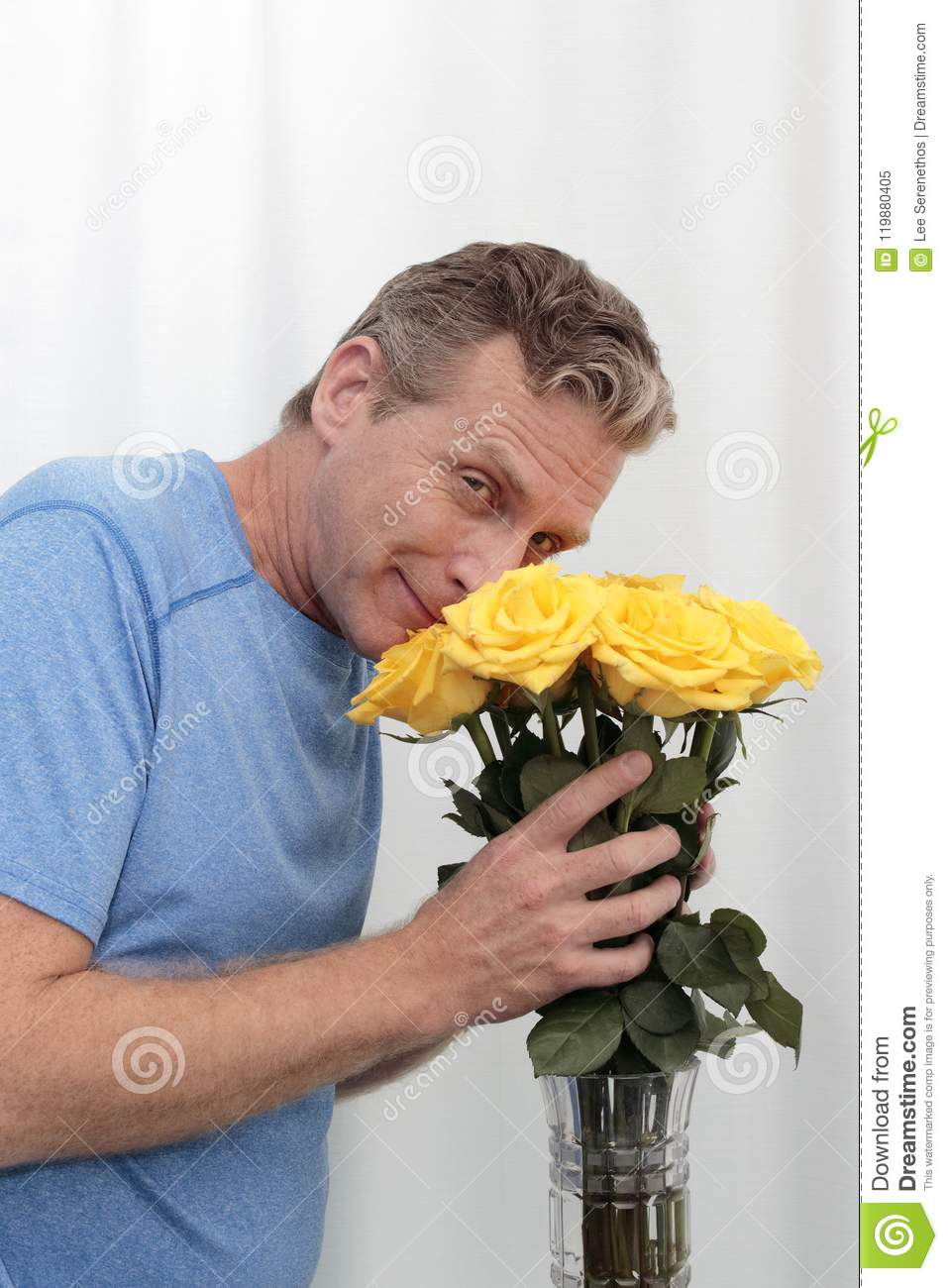 Man Smiling Holds and Smells Yellow Roses Bouquet