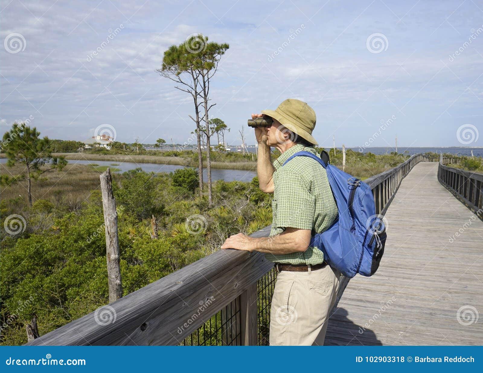 Man Birdwatching at Big Lagoon State Park in Florida
