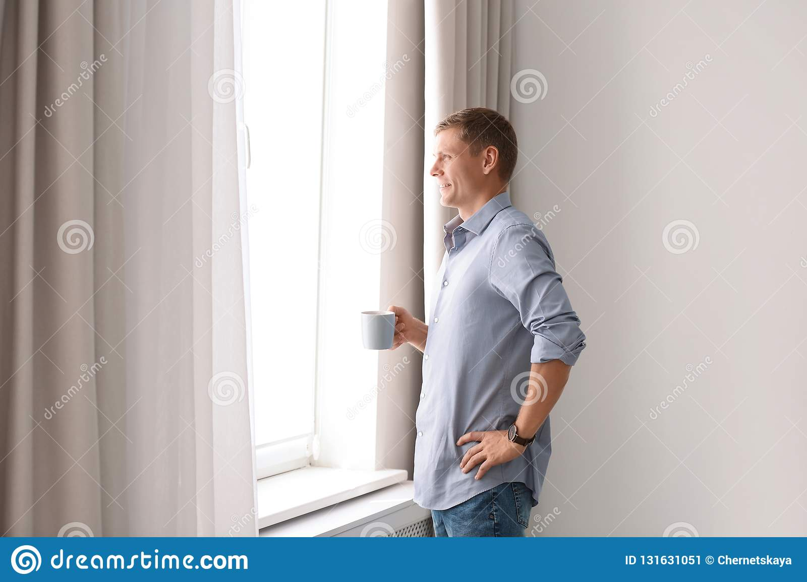 Mature man with cup of drink near window with open curtains at home