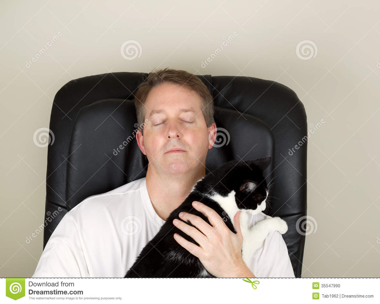 Photo of mature man wearing white shirt while relaxing in massage chair,  eyes closed, with hands holding black and white family cat