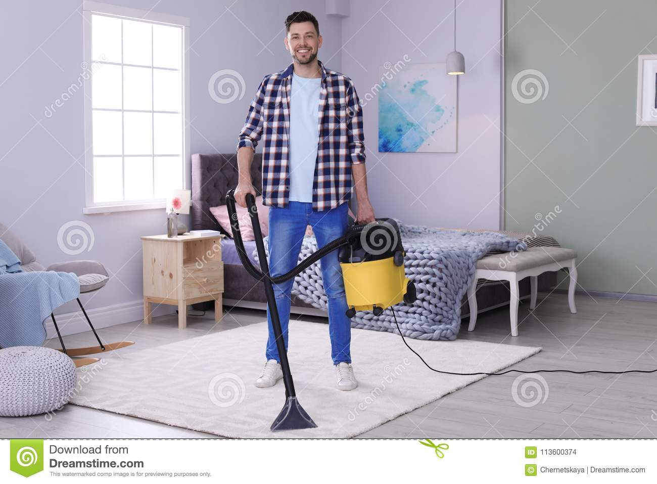 Mature man hoovering carpet with vacuum cleaner