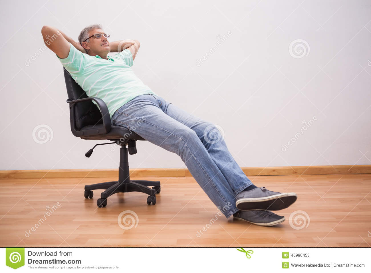 Mature Man Leaning Back In Swivel Chair Stock Photo