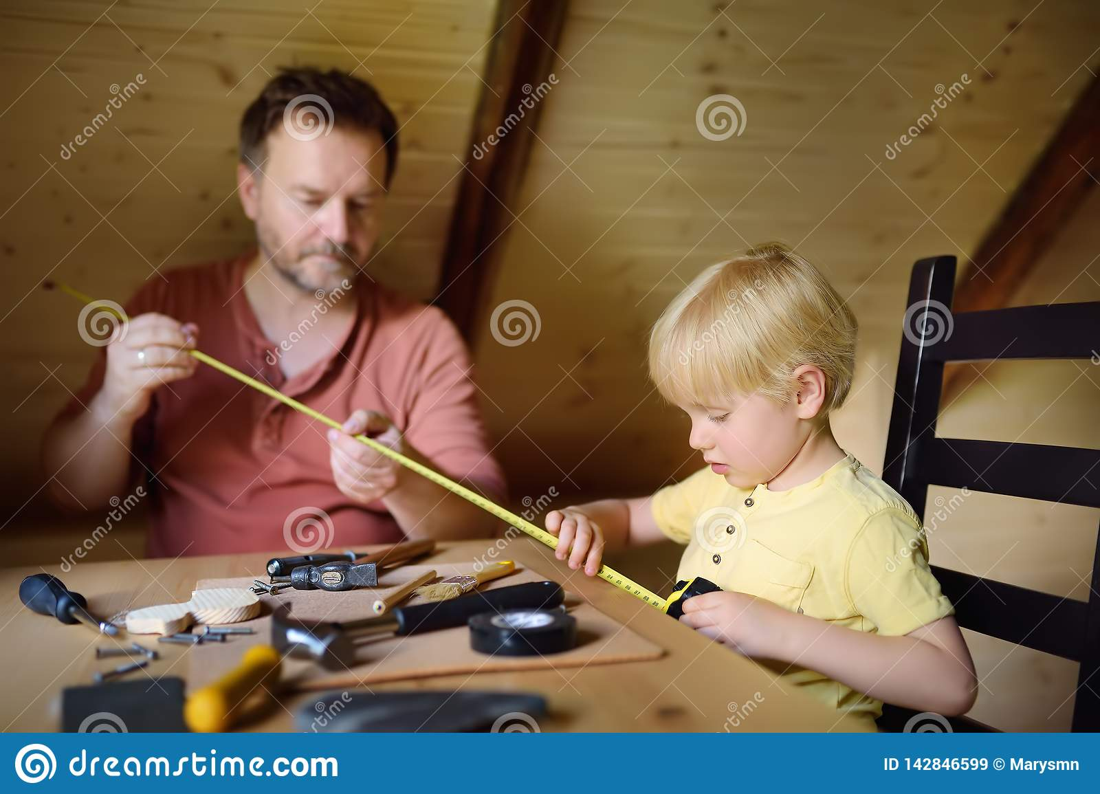 Mature man and little boy make a wooden toy together. Father learn his son work with tools.Traditional education of boy. Family`s