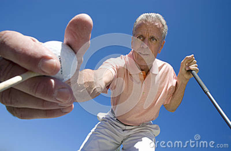 Mature man placing golf tee in grass on golf course, holding golf ball and club, close-up, upward view (wide angle)