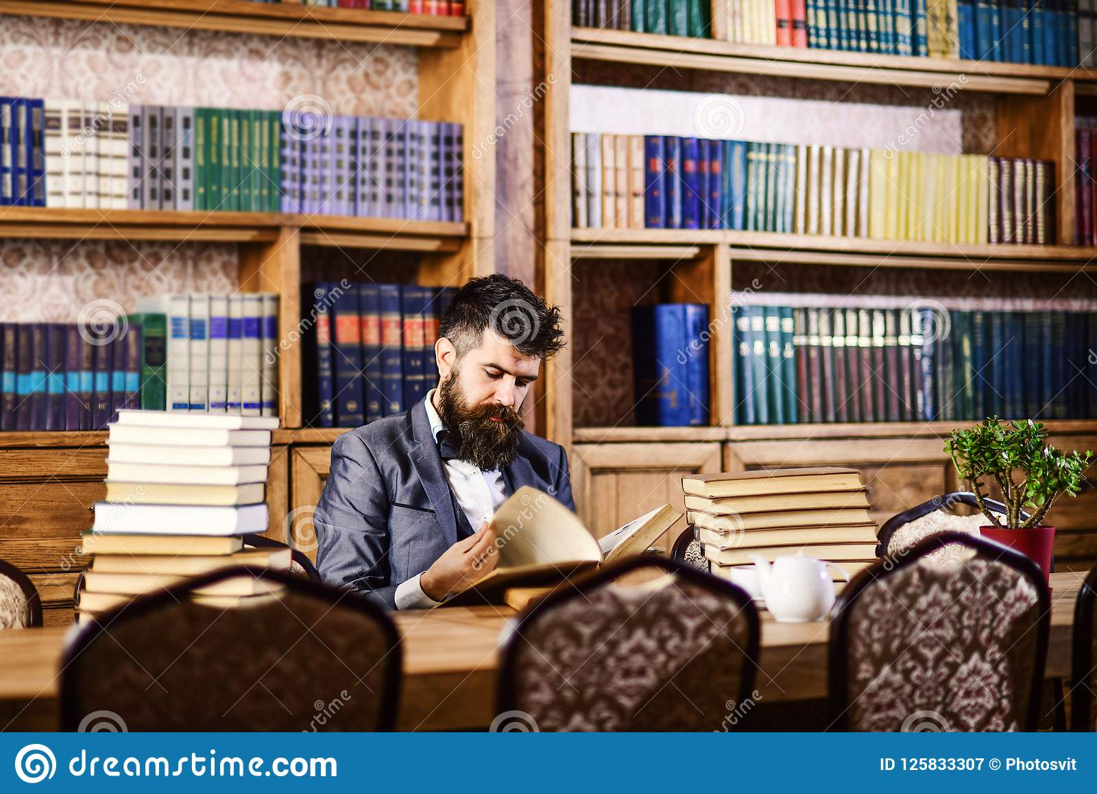 Mature man or professor with long beard and calm face. Historian sits in library and reads old books.