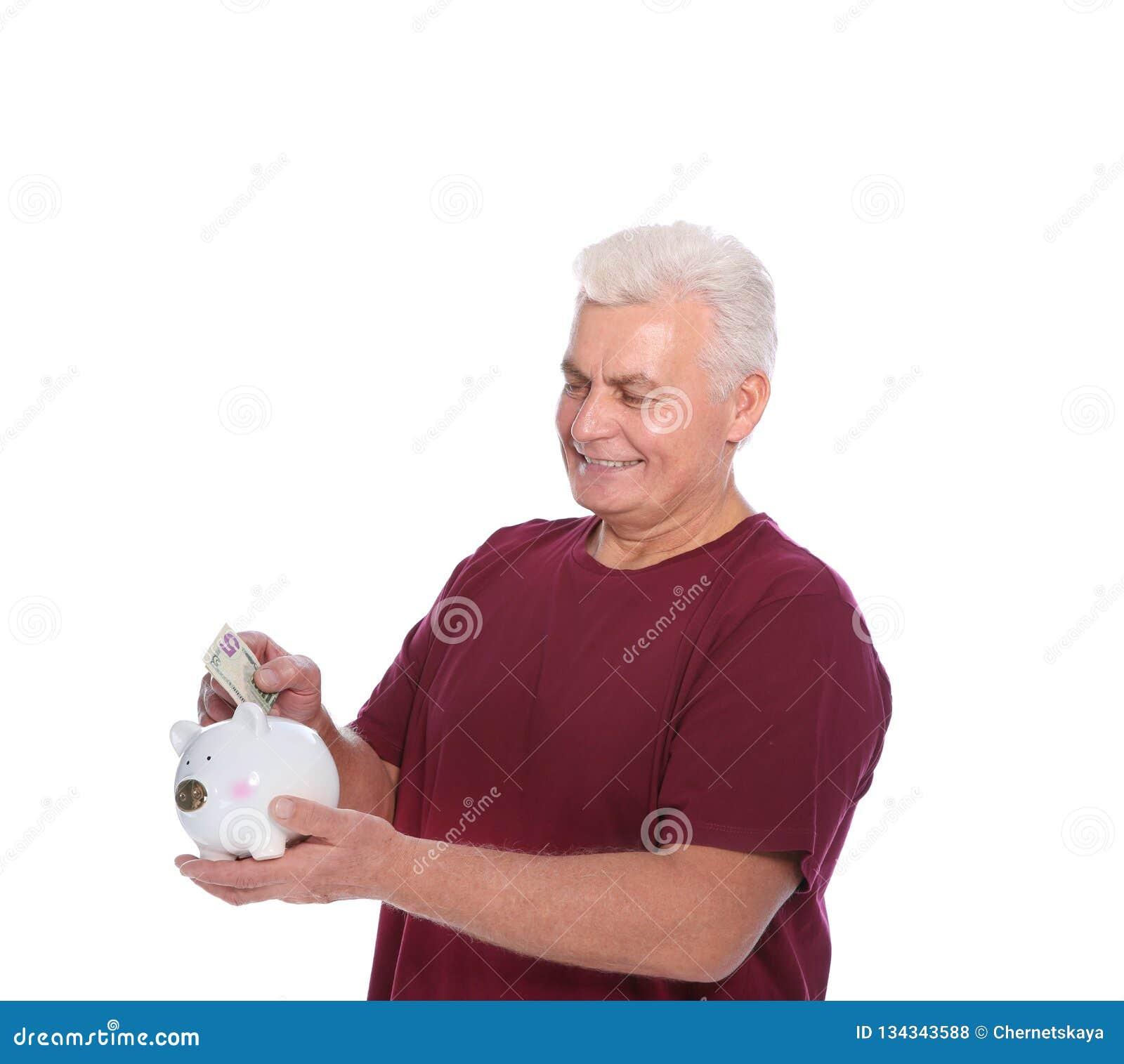 Mature man putting money into piggy bank