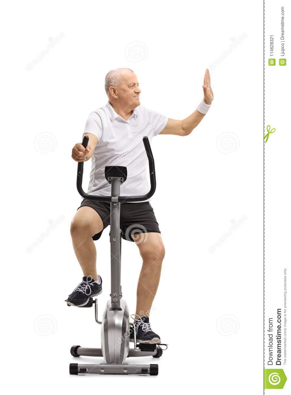 mature man riding a stationary bike and making a high-five gestu