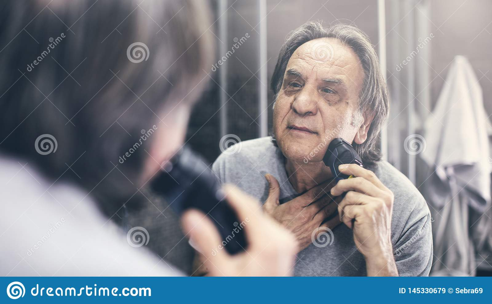 Mature man shaving in front of mirror