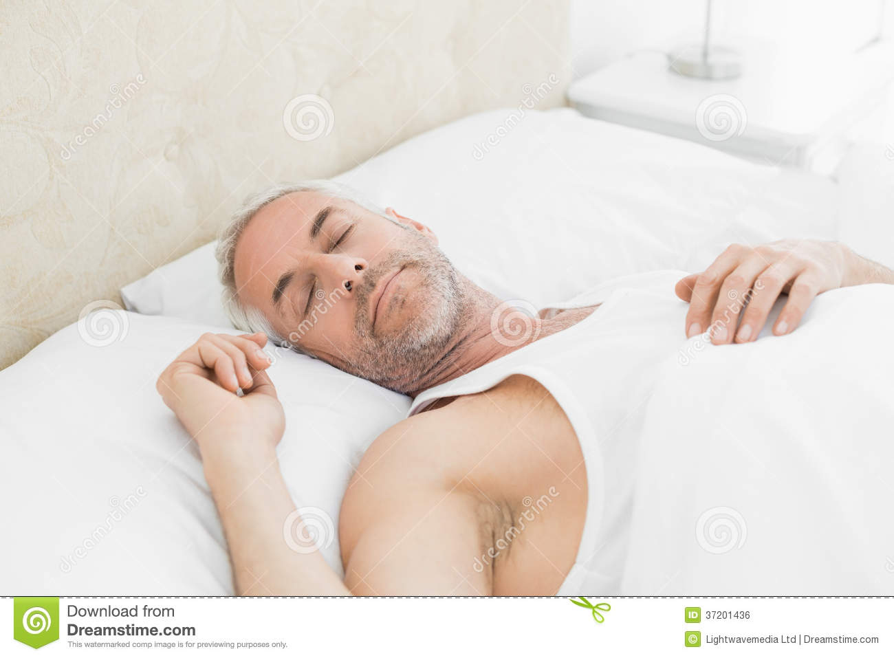 Mature man sleeping in bed at home