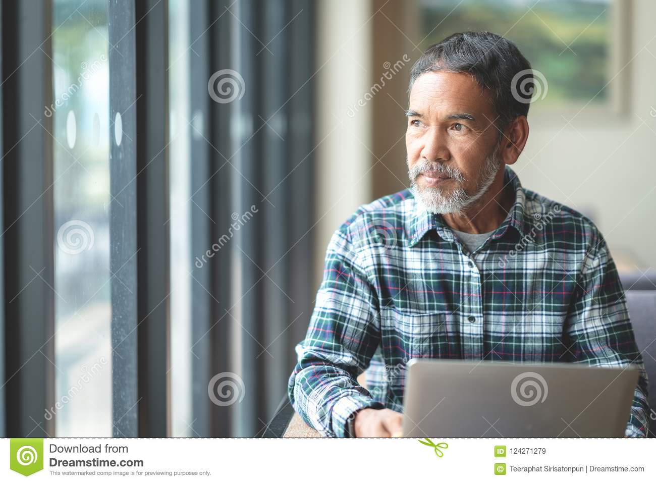Mature man with white stylish short beard looking outside window. Casual lifestyle of retired hispanic people