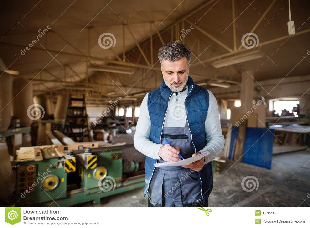 A Man Worker In The Carpentry Workshop, Making Plans  Stock