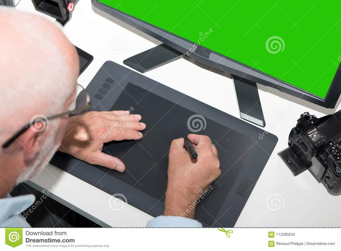 Mature man working with graphics tablet in office