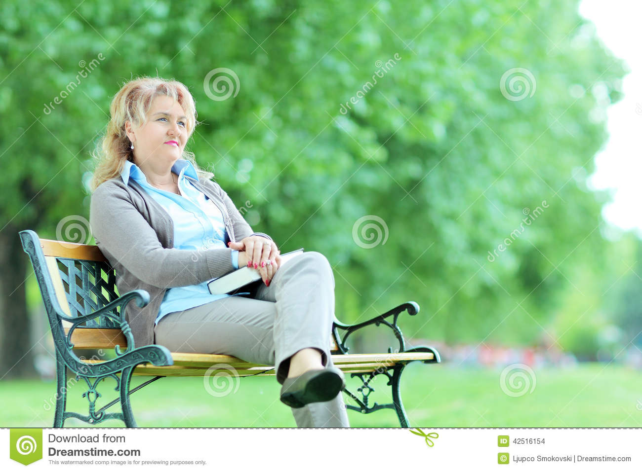 Mature pensive woman sitting alone in park