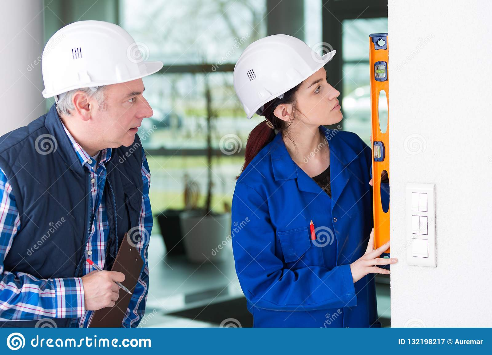 Mature repairman helping woman to use builder level