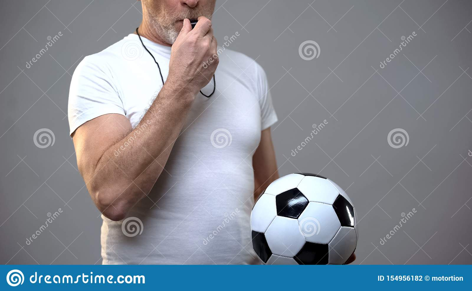Mature sportive man holding football ball and blowing whistle, coach, training