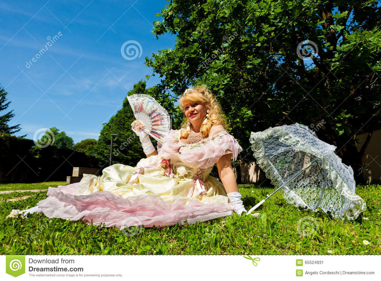 Mature vintage woman in Venetian costume lying on the green park with white umbrella