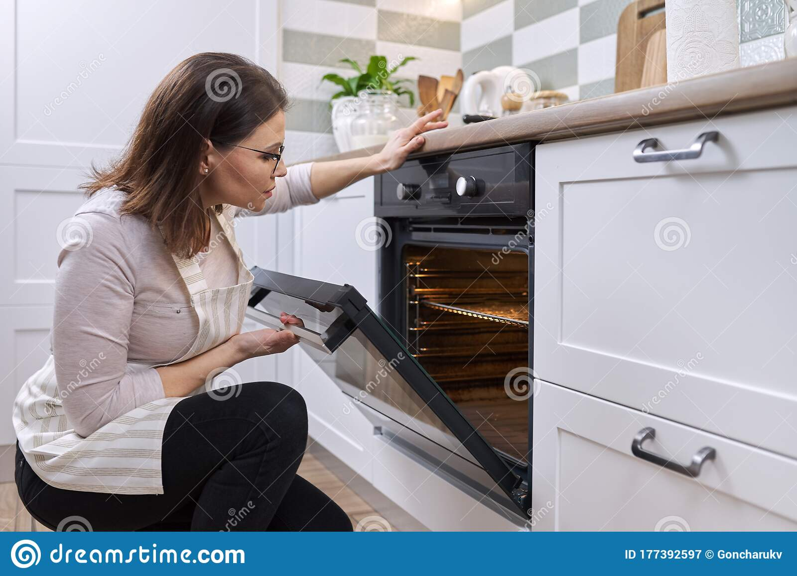 Housewife With Repairman Near Modern Oven Stock Photo