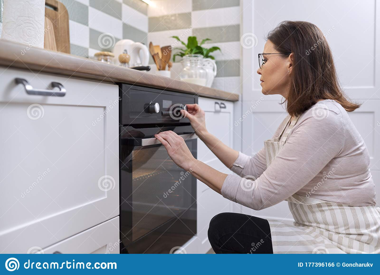 Hand Holding Paper Towels In Kitchen Near Refrigerator