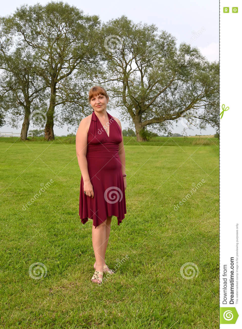 The mature woman costs on a meadow.