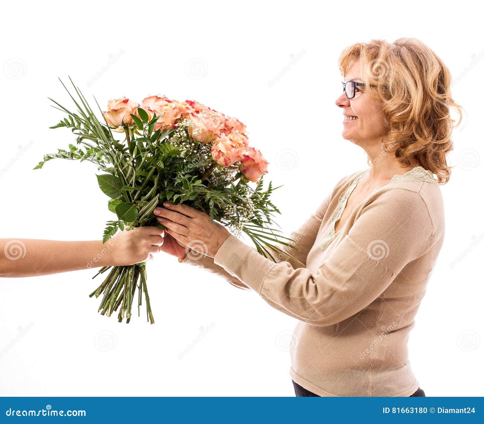 A mulher madura obtém um ramalhete das rosas, dia do ` s da mãe, isolado