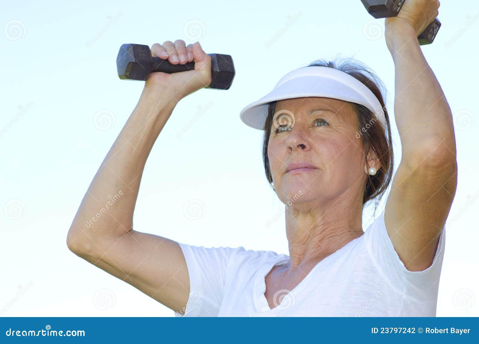 Mature woman lifting weights II