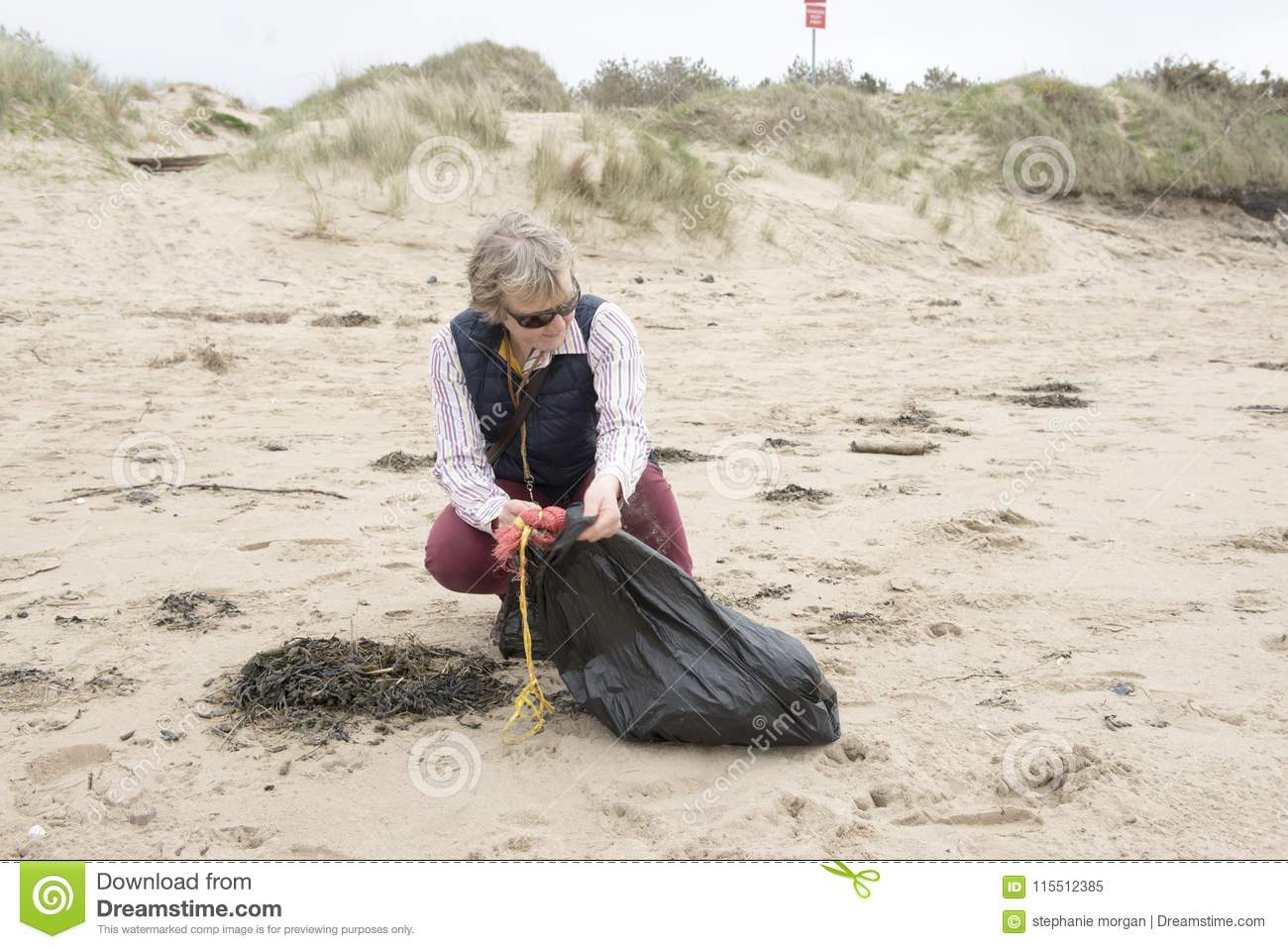 Mature Woman Picking Up Litter From A Beach Stock Image