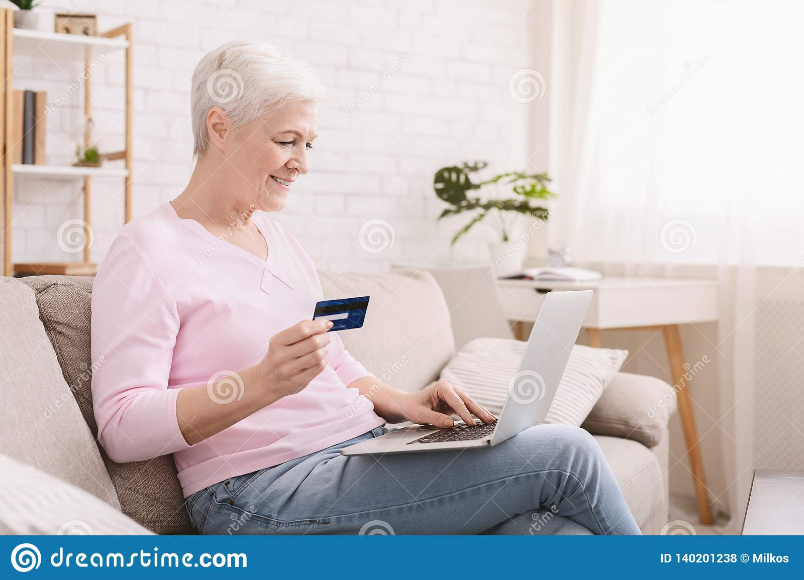 Mature woman shopping online with credit card and laptop