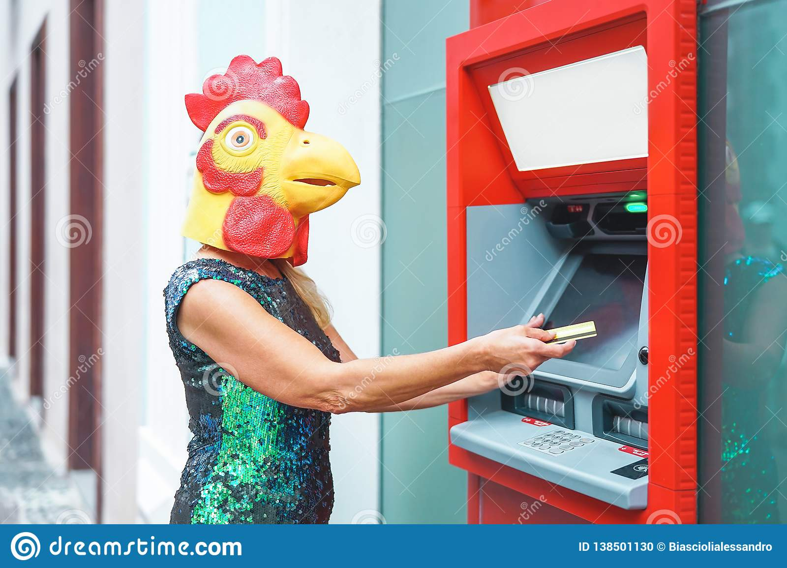 Mature woman wearing mask withdraw money from bank cash machine with debit card - Surreal image of half human and animal