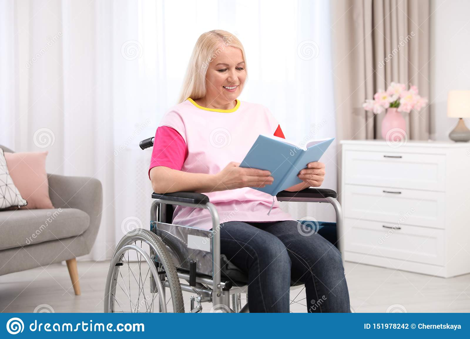 Mature woman in wheelchair with book