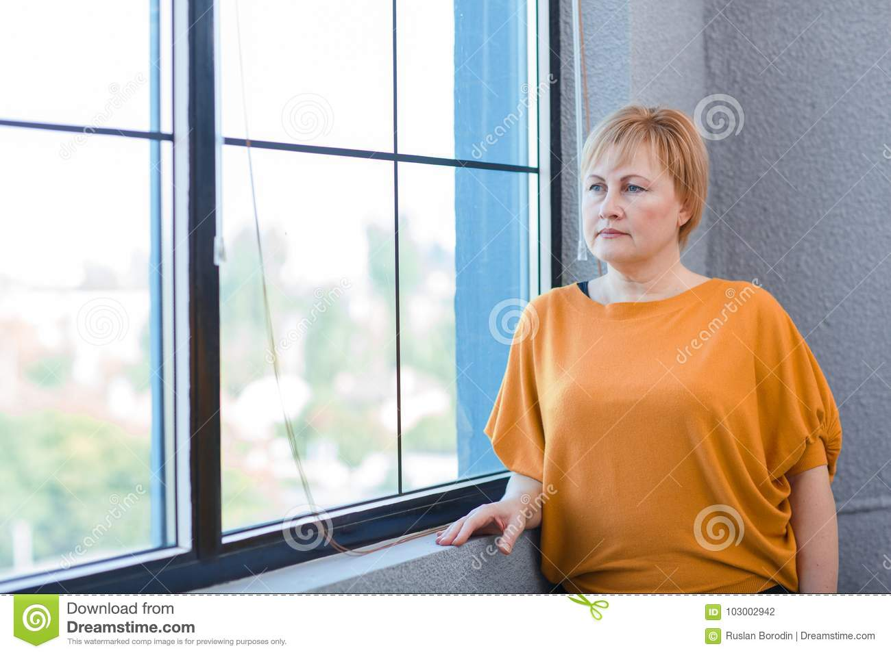 Mature woman in a yellow blouse looks out the window.