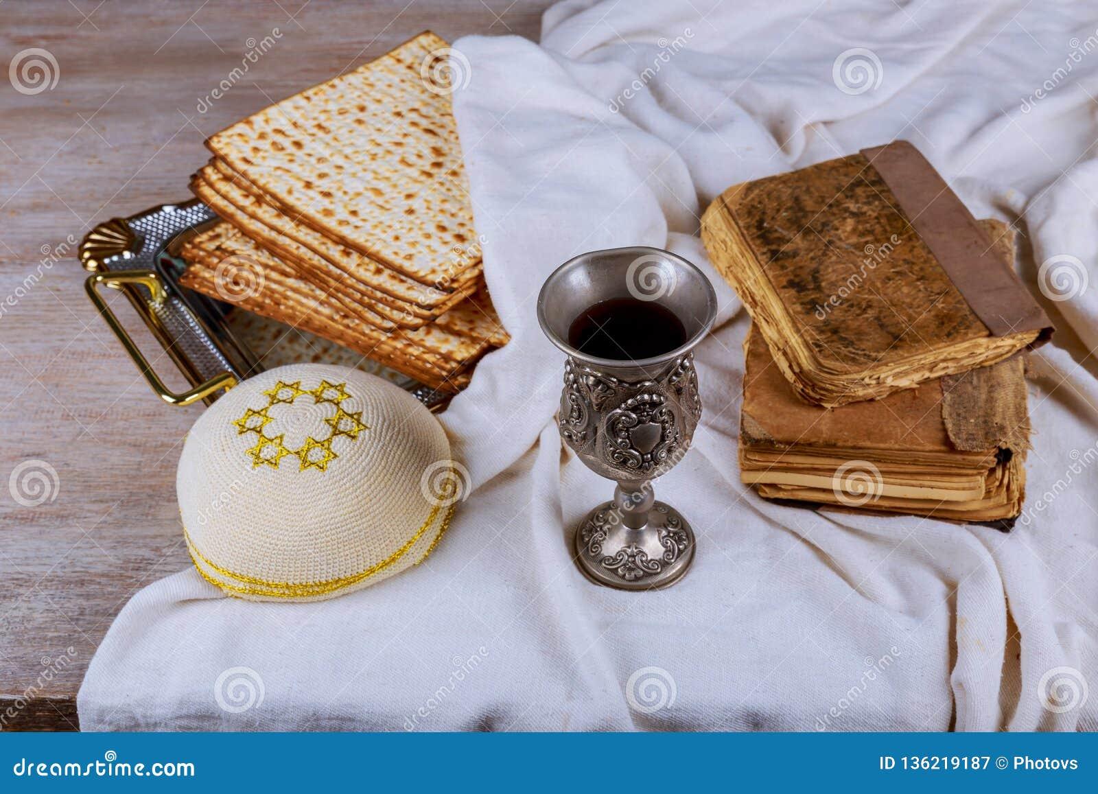 Matzo para la pascua judía con la bandeja y el vino del metal en la tabla