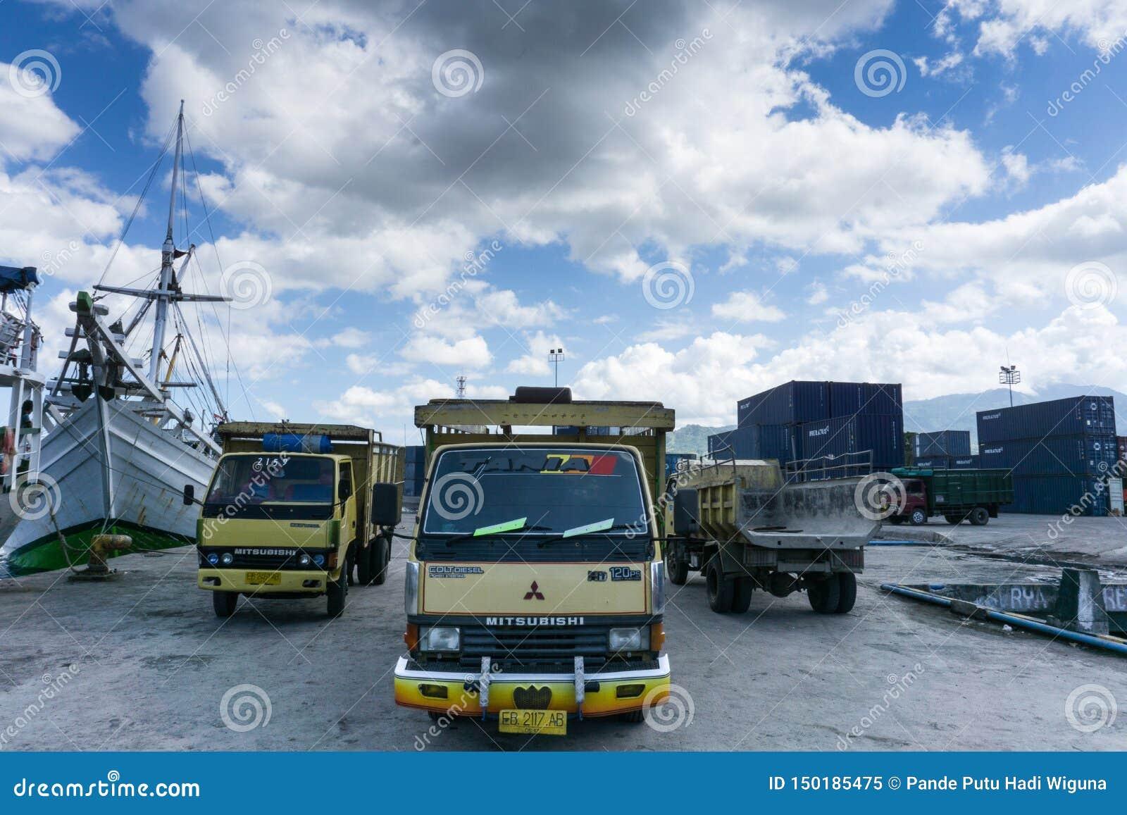 MAUMERE/INDONESIA-APRIL 28 2014年:运载物品的三辆卡车在港停放了毛梅雷在一个晴天,等待