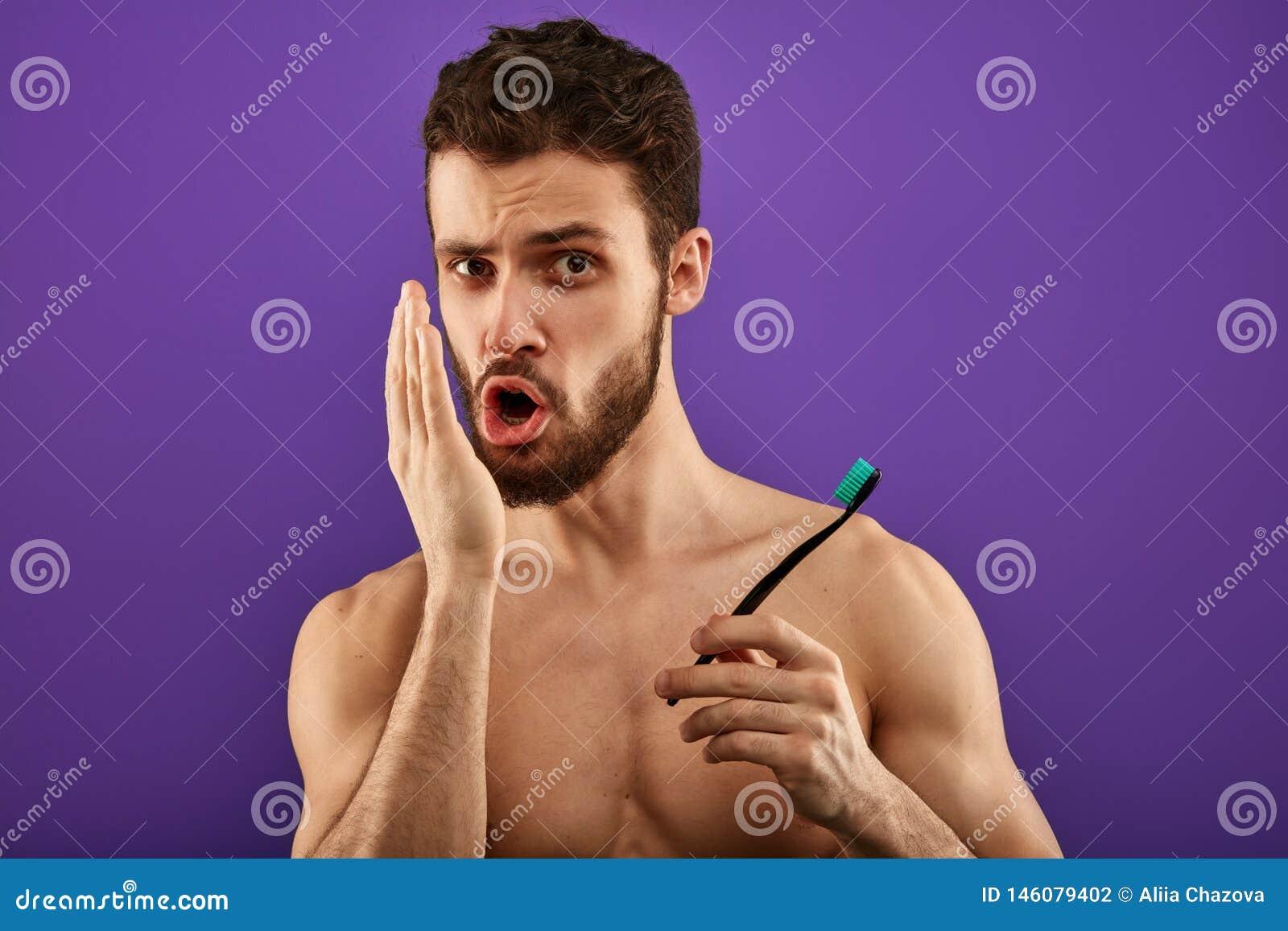 Mauvaise haleine douce de com?dien de souffle Jeune homme bel vérifiant son souffle avec sa main