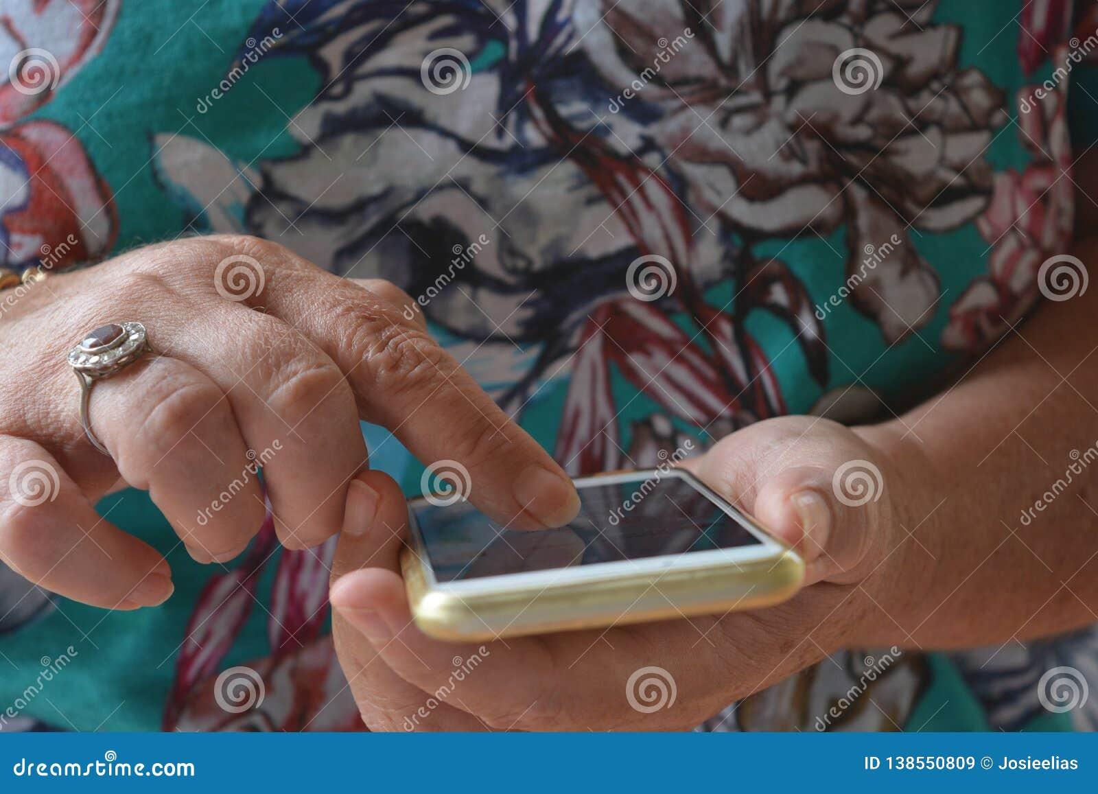 Mayor usando la pantalla táctil de un teléfono móvil, al aire libre