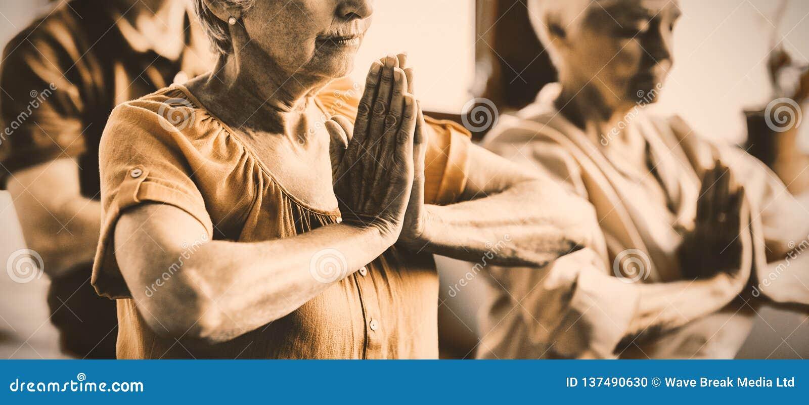 Mayores que hacen yoga con los ojos cerrados