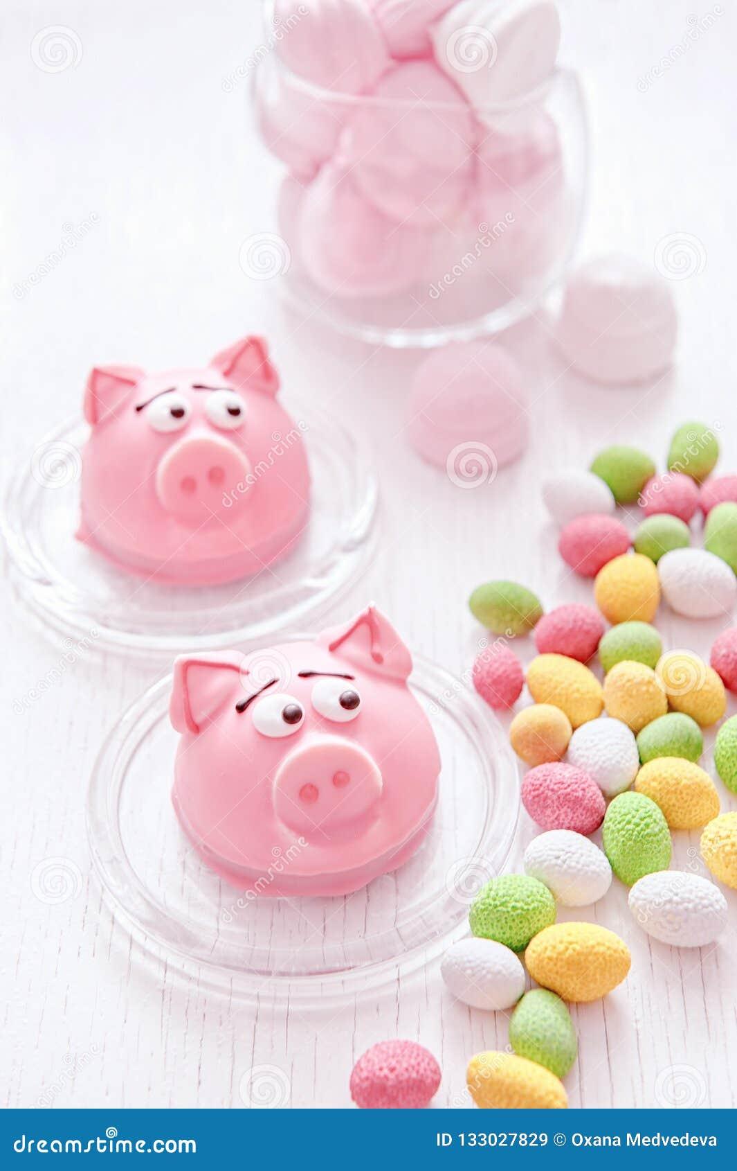 Mazapán en la forma del símbolo del Año Nuevo - cerdo rosado, macarrones delicados dulces, melcochas, cacahuetes en azúcar