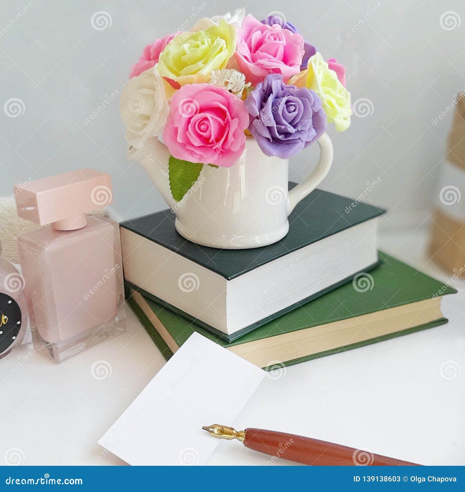 Mazzo delle rose in un vaso, pila di libri, carta con la penna della montagna sulla tavola davanti a fondo bianco
