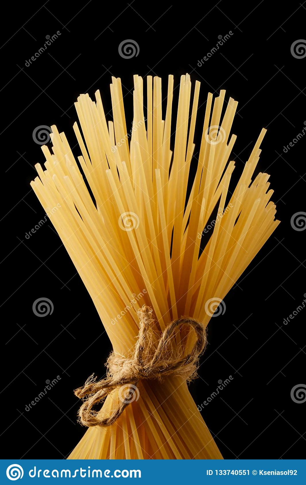 Mazzo di spaghetti legati con la corda Pasta italiana gialla Spaghetti lunghi Isolato su un fondo nero
