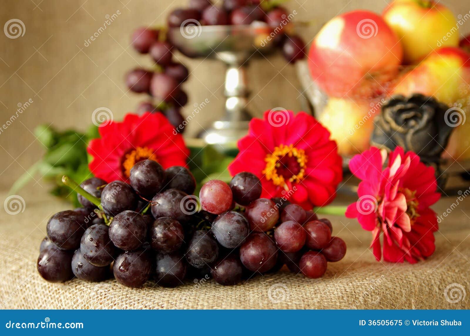 Mazzo di uva matura su un fondo dei colori luminosi e dei vasi con le mele