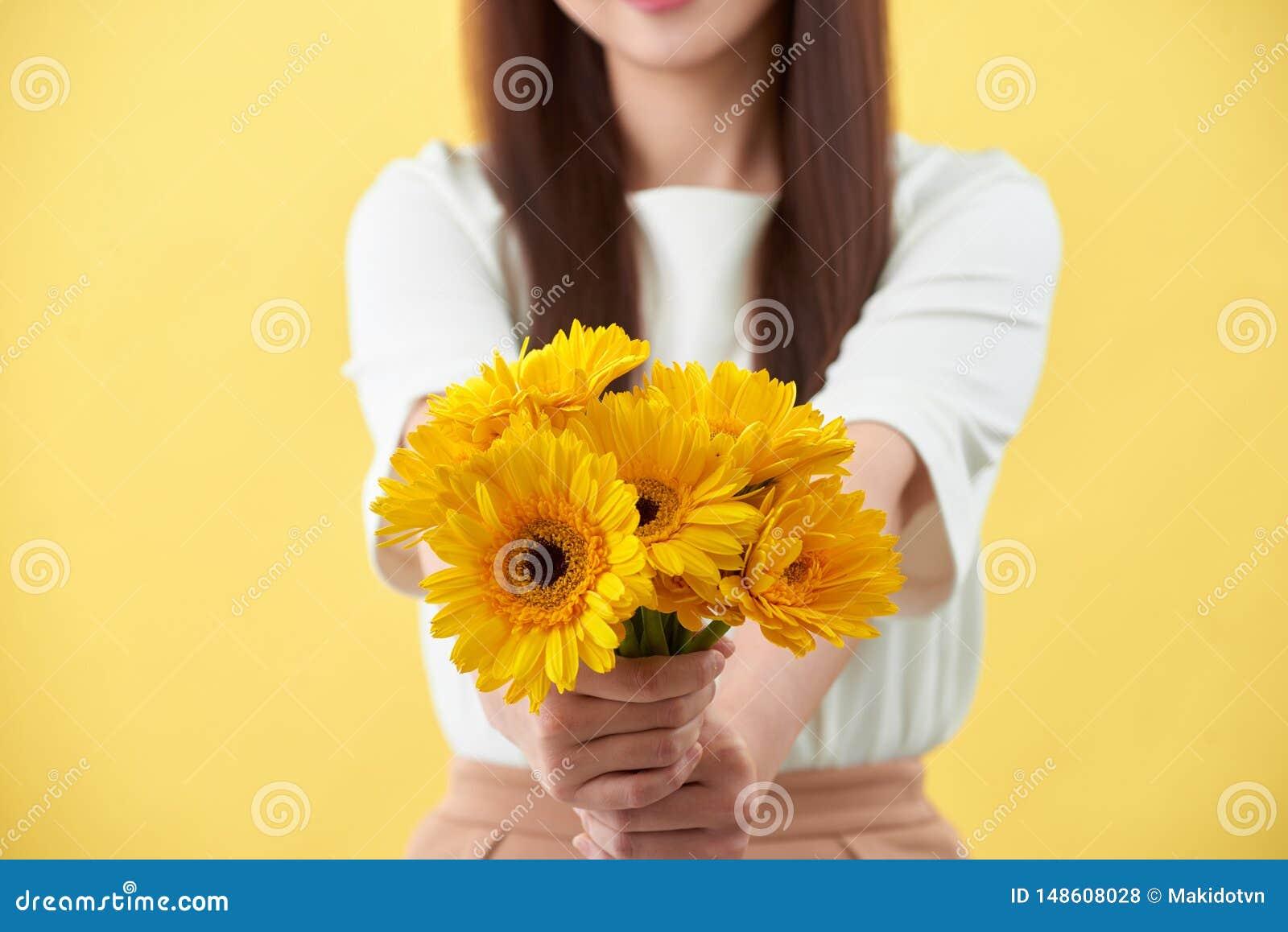 Mazzo felice della tenuta della giovane donna dei fiori in sua mano su fondo giallo