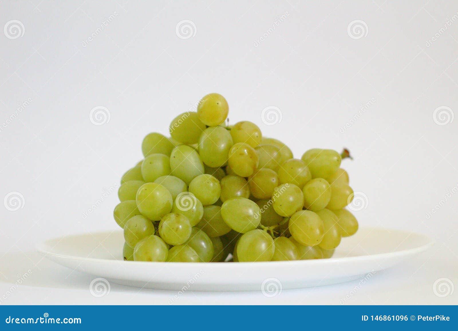 Mazzo isolato di uva su un piatto