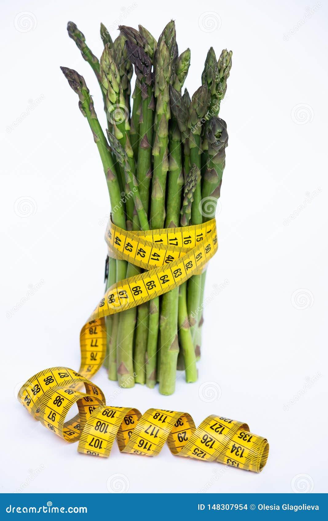 Mazzo verde fresco dell asparago con nastro adesivo di misurazione isolato sopra fondo bianco
