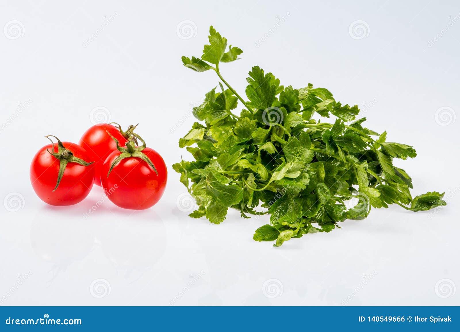 Mazzo verde fresco maturo di prezzemolo con tre pomodori, ingrediente brillante su fondo bianco