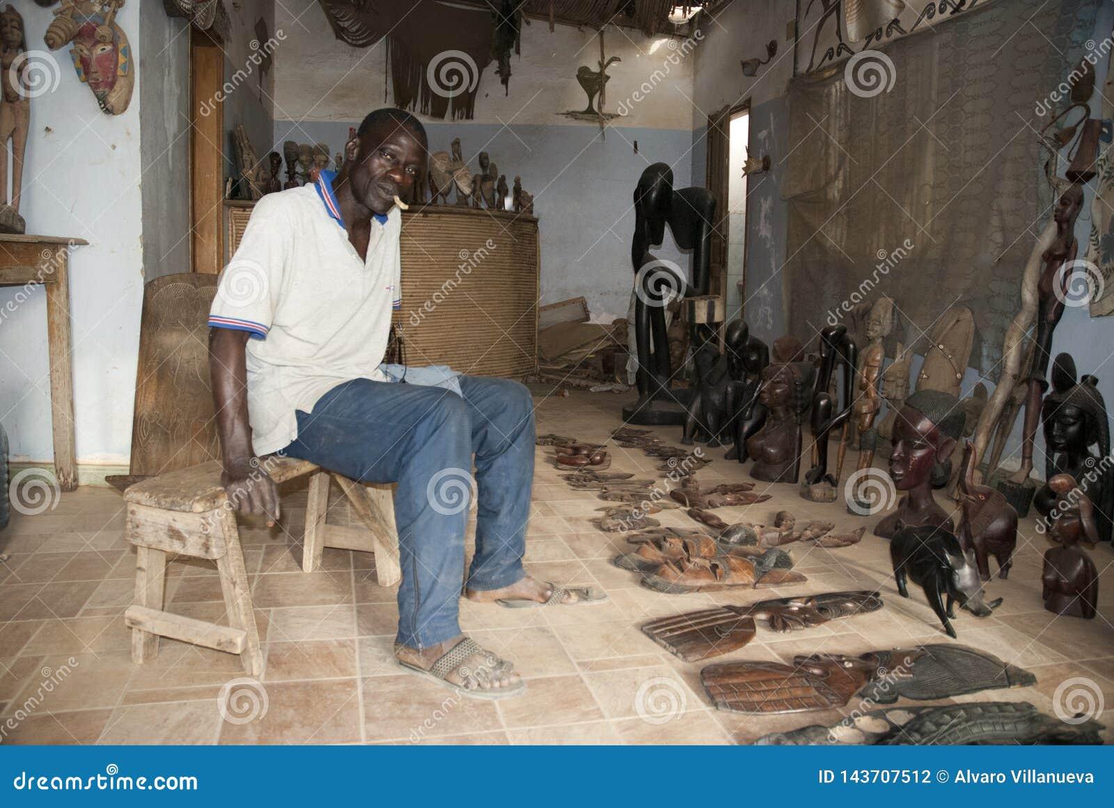 Mbour, Senegal, handcrafts seller posing inside his small shop