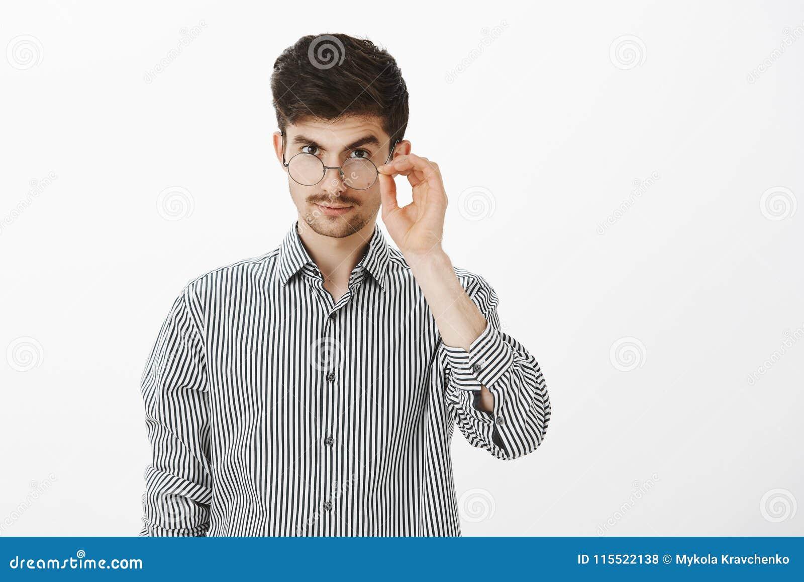 Me intrigan Compañero de trabajo masculino caucásico joven confiado hermoso, mirando de debajo la frente con la ceja levantada