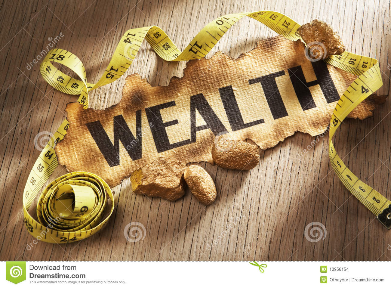Measuring wealth concept using burnt paper with word wealth printed on ...