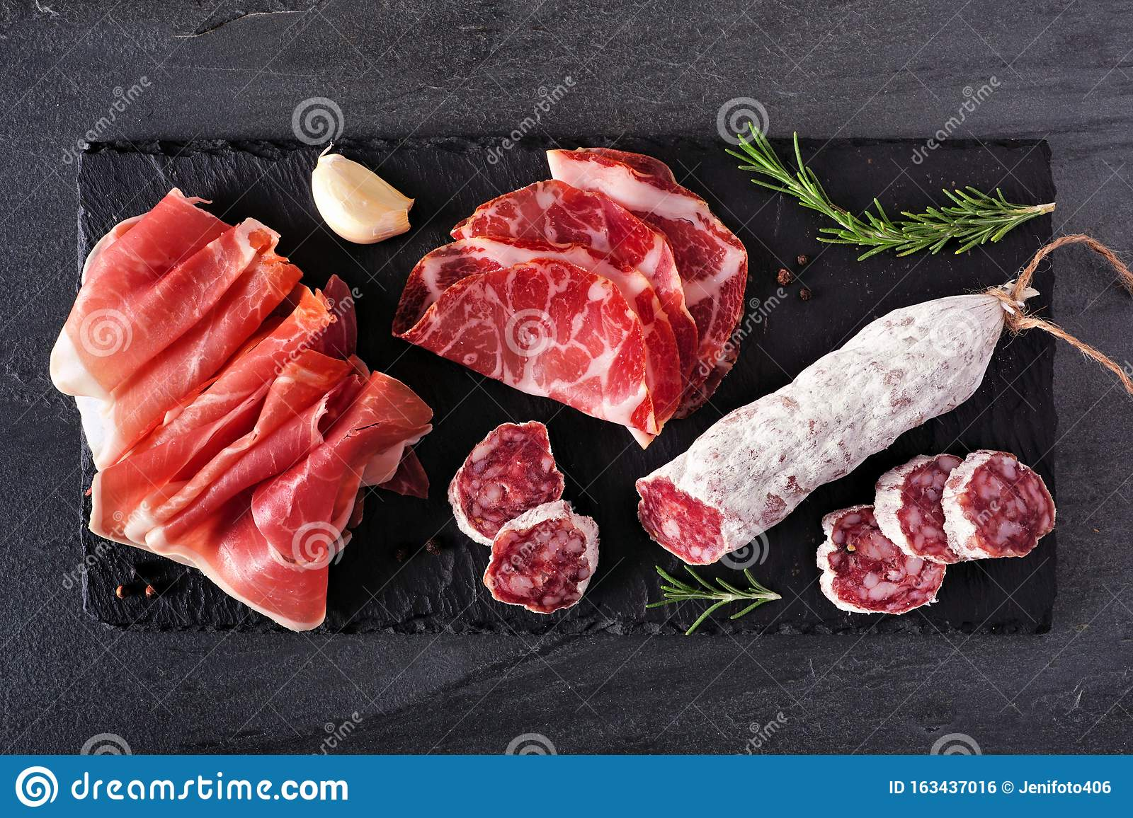 Meat appetizer platter with sausage, and cold cuts, above view on a slate serving board