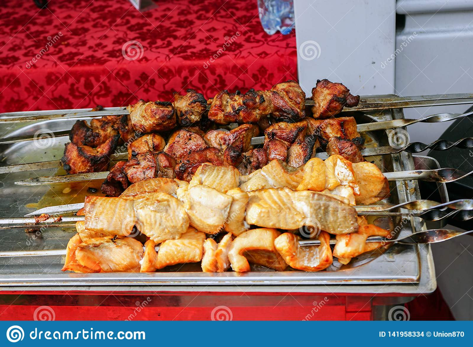 Meat cooked on the grill is on a metal tray