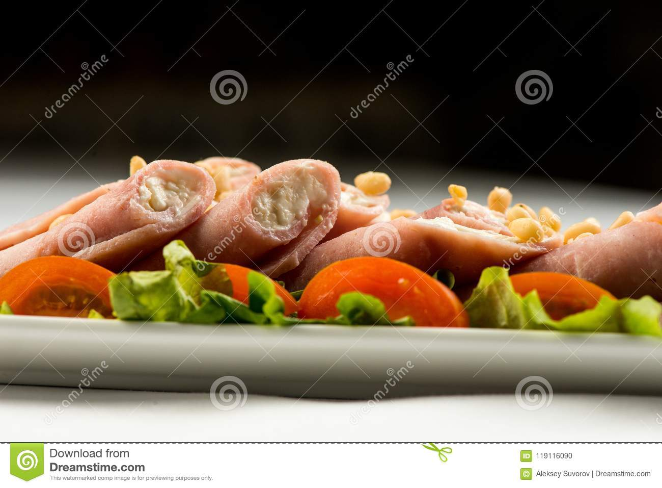 Meat rolls with ham, cheese and greens, on white background